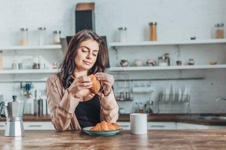 jeune belle femme petit déjeuner avec croissants et café à table en bois dans la cuisine à la maison
