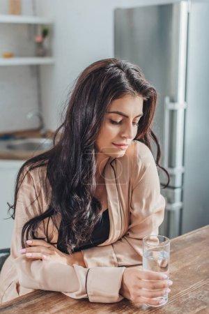 belle jeune femme tenant verre avec de l'eau et assise à la table en bois dans la cuisine à la maison