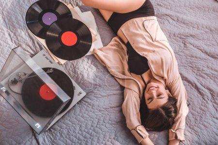 Photo pour Vue grand angle de fille couchée sur le lit et écoutant lecteur audio vinyle à la maison - image libre de droit