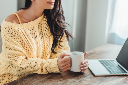 Photo for Partial view of female freelancer holding coffee cup and sitting at wooden table with laptop in kitchen at home - Royalty Free Image