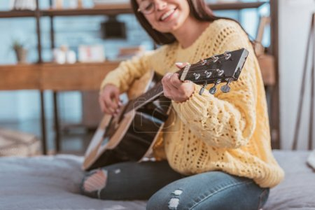 Photo for Selective focus of girl in eyeglasses playing on acoustic guitar while sitting on bed at home - Royalty Free Image