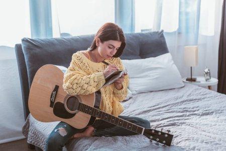 Photo pour Belle fille assis avec la guitare acoustique et l'écriture de chanson en manuel sur lit à la maison - image libre de droit