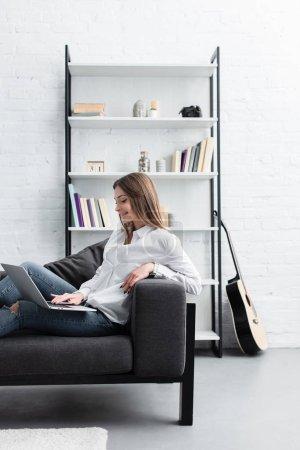 Foto de Niña sonriente sentado en sofá y uso portátil en la sala de estar - Imagen libre de derechos