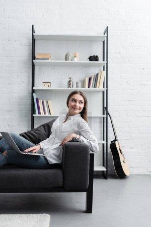 Photo pour Belle fille souriante assis sur le canapé et utilisez l'ordinateur portable dans le salon - image libre de droit