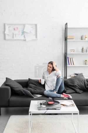 Photo pour Girl sitting on couch with coffee cup, using laptop and listening to vinyl record player in living room - image libre de droit