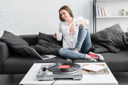 Photo pour Girl in white shirt sitting on couch with coffee cup, using laptop and listening to vinyl record player in living room - image libre de droit