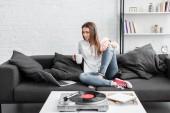 """Постер, картина, фотообои """"красивая девушка в белой рубашке, сидя на диване с чашкой кофе, используя ноутбук и слушать виниловый проигрыватель в гостиной"""""""