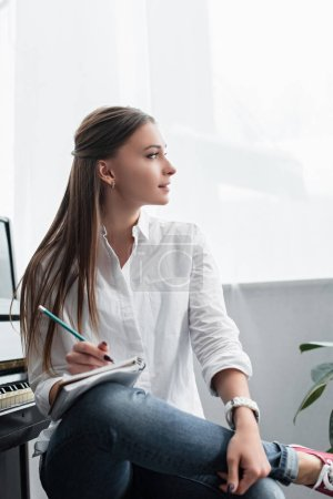 beautiful girl in white shirt sitting and writing in notebook at home