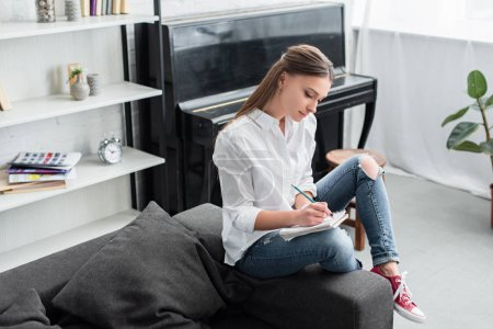 girl with notebook sitting on couch and composing music with piano on background in living room