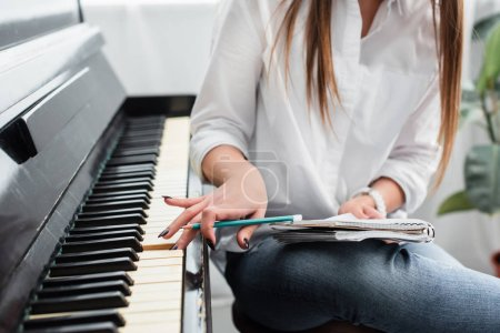 Photo for Cropped view of girl in white shirt with notebook playing piano and composing music at home - Royalty Free Image