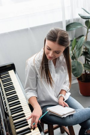Photo for Attractive girl with notebook playing piano and composing music at home - Royalty Free Image