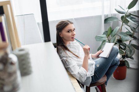 Photo for Beautiful girl with notebook sitting near piano, biting pencil and looking at camera while composing music in living room - Royalty Free Image