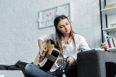 Photo pour Belle fille assise sur le canapé avec la guitare, écrire dans cahier et composer de la musique dans le salon - image libre de droit