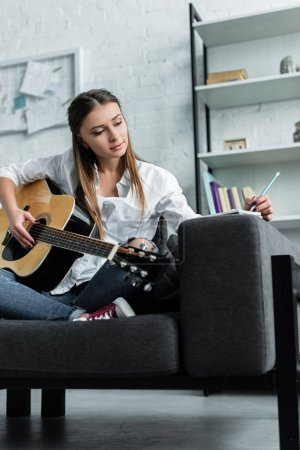 Photo pour Fille pensive assis sur le canapé avec la guitare, écrire dans cahier et composer de la musique dans le salon - image libre de droit