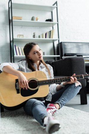 beautiful pensive girl sitting and playing guitar in living room