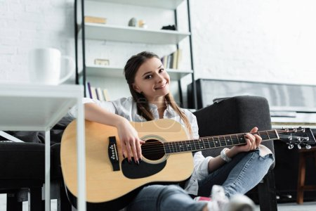 Photo for Beautiful smiling girl sitting and playing guitar in living room - Royalty Free Image