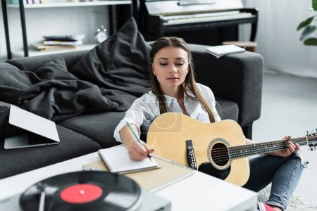 Photo for Selective focus of girl with acoustic guitar writing in notebook while composing music at home - Royalty Free Image