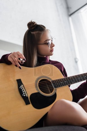 beautiful girl sitting, holding marijuana joint and playing guitar at home
