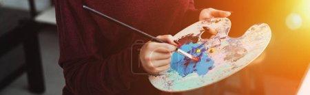 Photo pour Vue partielle de fille tenant pinceau avec palette et peinture à la maison avec rétro-éclairé - image libre de droit