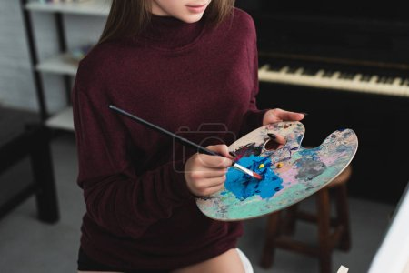 partial view of girl in burgundy sweater holding paintbrush with palette and painting at home