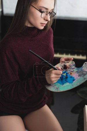 Foto de Hermosa chica en un Borgoña suéter sentada, holding pincel, paleta y pintura en casa - Imagen libre de derechos
