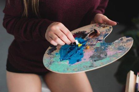 Foto de Vista recortada de niña en Borgoña suéter sentada con paleta y pintura en casa - Imagen libre de derechos
