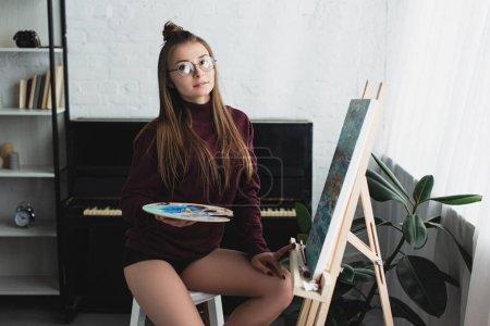 Foto de Chica en Borgoña suéter sentada y mirando a cámara mientras pintura en casa - Imagen libre de derechos