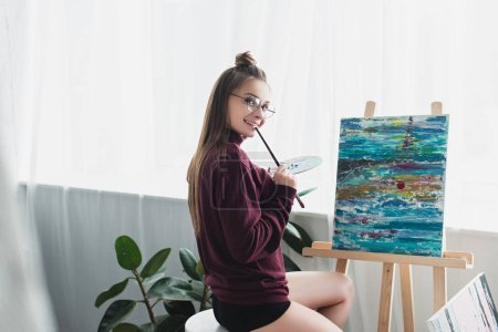 Photo for Smiling girl in glasses sitting in front of easel, holding paintbrush and palette and looking at camera in living room - Royalty Free Image