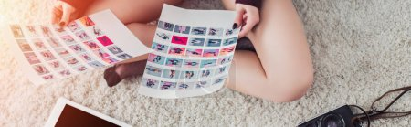 Photo for Cropped view of photographer holding pictures and sitting on carpet - Royalty Free Image