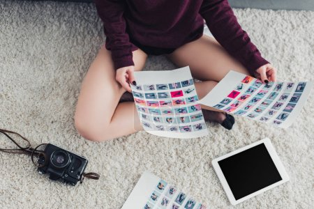 Photo for Cropped view of photographer sitting on carpet and holding pictures - Royalty Free Image