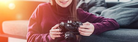 Photo for Cropped view of smiling photographer sitting on floor near sofa and holding film camera - Royalty Free Image