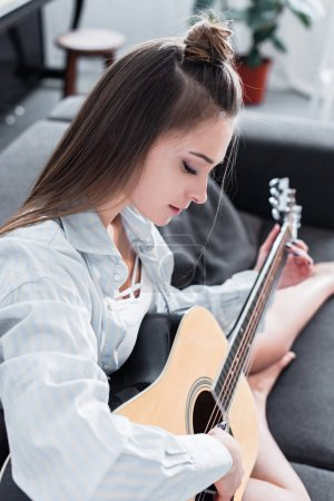 beautiful musician in shirt sitting on sofa and playing acoustic guitar in living room