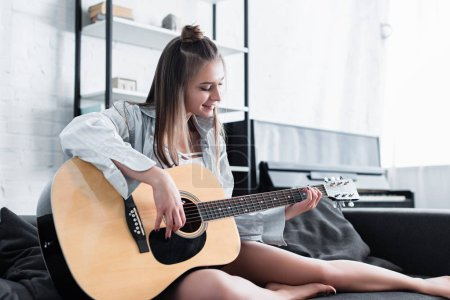 beautiful musician sitting on sofa, smiling and playing acoustic guitar at home
