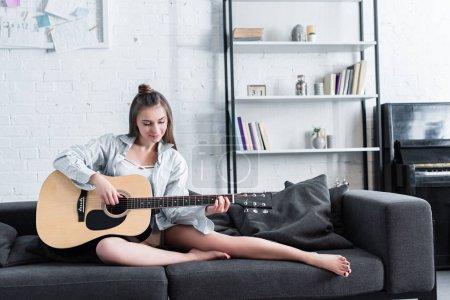 Photo pour Magnifique musicien assis sur le canapé et jouer de la guitare acoustique à la maison - image libre de droit