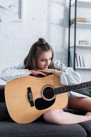 Photo pour Musicien pensif assis sur le canapé et tenant une guitare acoustique à la maison - image libre de droit