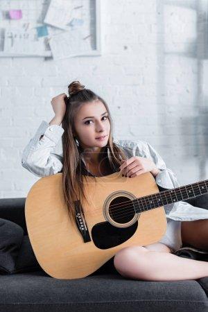 Foto de Atractivo músico sentado en sofá, sosteniendo la guitarra acústica y mirando a cámara en casa - Imagen libre de derechos