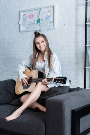 Photo for Smiling musician sitting on couch and playing acoustic guitar at home - Royalty Free Image
