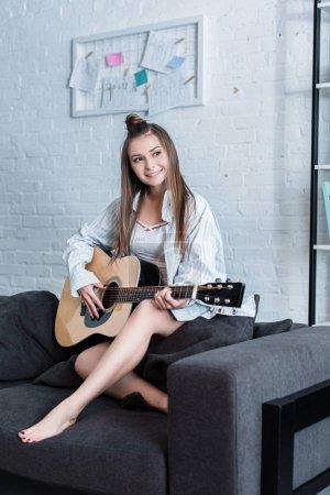Photo pour Souriant le musicien assis sur le canapé et jouer de la guitare acoustique à la maison - image libre de droit