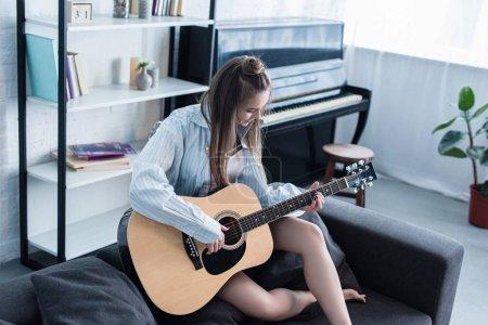 Foto de Músico sentado en sofá y tocar la guitarra acústica en sala de estar - Imagen libre de derechos