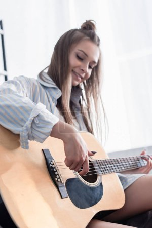 cheerful musician playing acoustic guitar at home