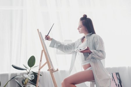 side view of attractive artist holding palette and painting on canvas at home