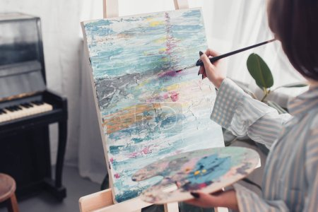 Photo for Artist holding palette and painting on canvas at home - Royalty Free Image