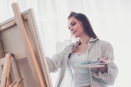 attractive artist holding palette and looking at easel in living room