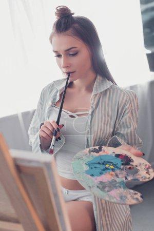 Photo pour Séduisante artiste tenant palette, mordre pinceau et chevalet dans le salon en regardant - image libre de droit