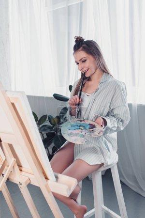 Photo pour Séduisante artiste assis sur une chaise, tenant la palette, mordre pinceau et chevalet dans le salon en regardant - image libre de droit
