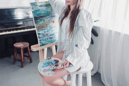 vista recortada del artista sentado en la silla delante del caballete y la celebración de la paleta en la sala de estar