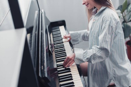 Photo for Cropped view of musician playing piano and smiling in living room - Royalty Free Image