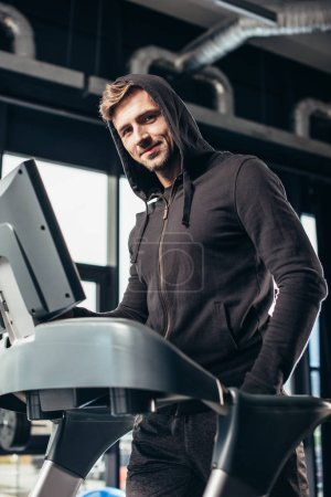 Photo for Handsome sportsman in hoodie exercising on treadmill in gym and looking at camera - Royalty Free Image