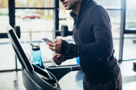 cropped image of sportsman in hoodie exercising on treadmill and using smartphone in gym