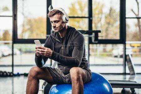 Photo pour Beau sportif utilisant un smartphone et assis sur une balle de fitness dans la salle de gym - image libre de droit